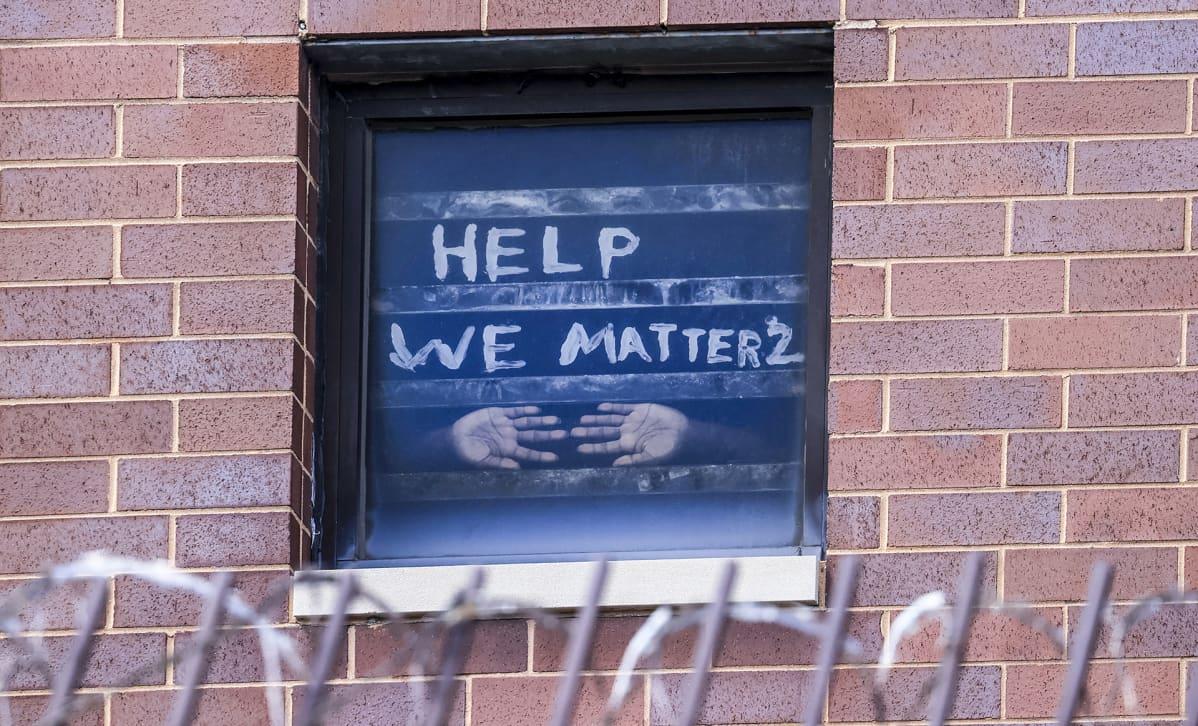 """Vangin kädet vankilan ikkunassa tekstin alla jossa lukee """"help, we matter""""."""