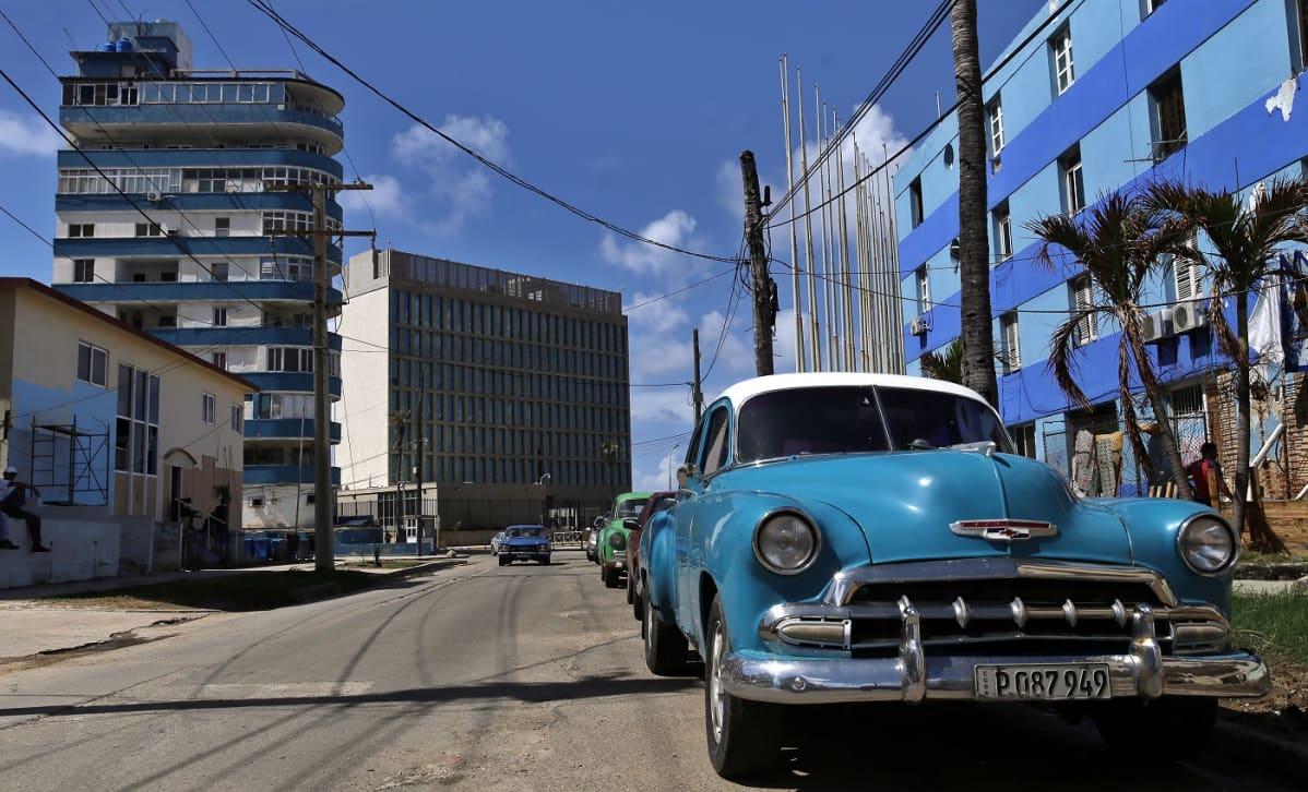 Sininen auto sinisen talon edessä.