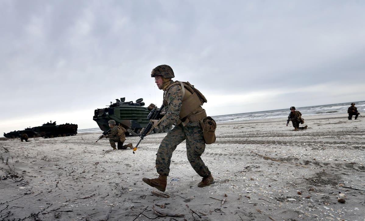 Maastoasuiset sotilaat  etenevät rannalla. Taustalla näkyy maihinnousualuksia. Taivas on pilvinen.