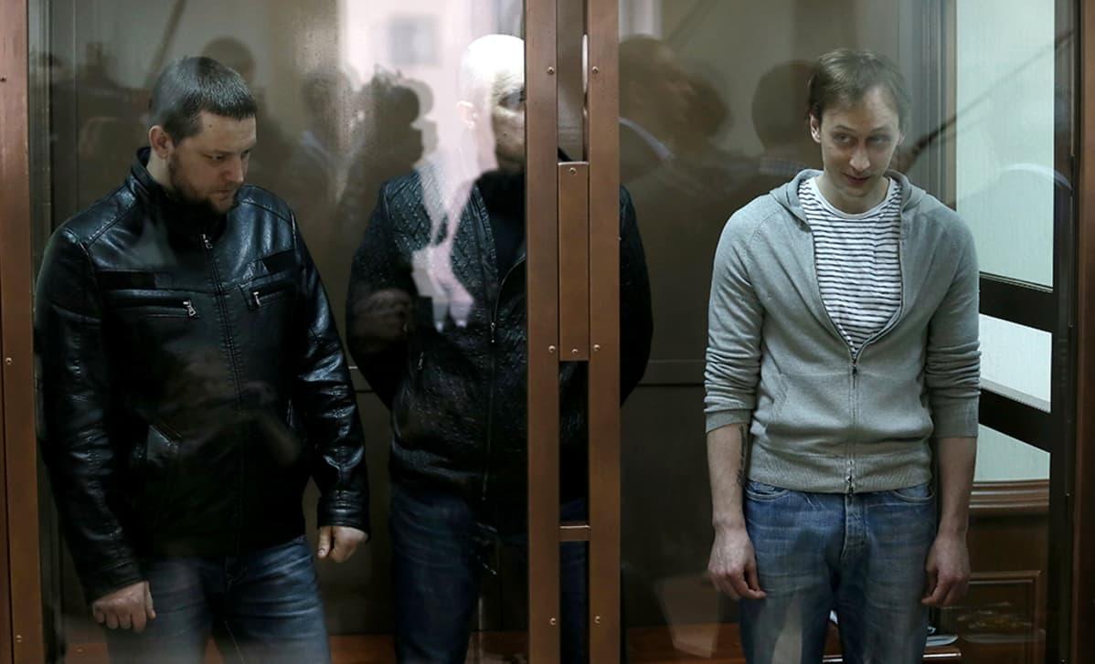 kolme miestä lasiseinäisessä kopissa