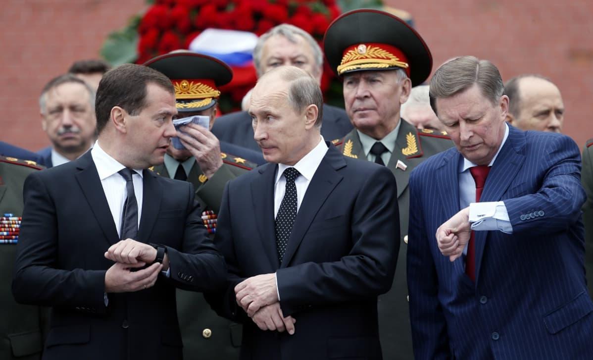 Venäjän pääministeri Dimitri Medvedev (vas.), presidentti Vladimir Putin ja hallintopäällikkö Sergei Ivanov (oik.) vierekkäin tutkimassa kellojaan. Taustalla sotilashenkilöitä.