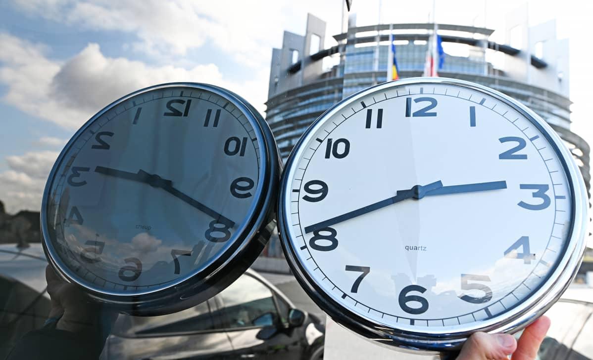 Käsi pitää kelloa ja Euroopan parlamenttirakennus Strasbourgissa siintää taustalla.