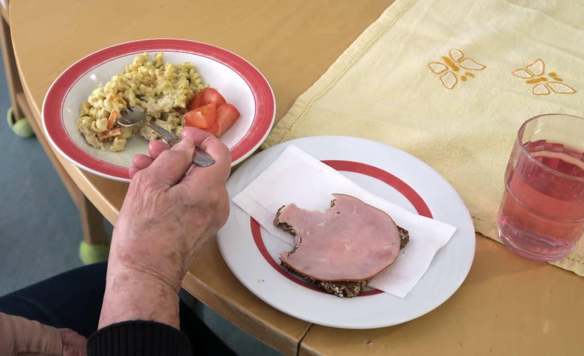 Iäkkään asiakkaan ateria: makaronia, tomaattia, voileipä, makkaransiivu, mehua.