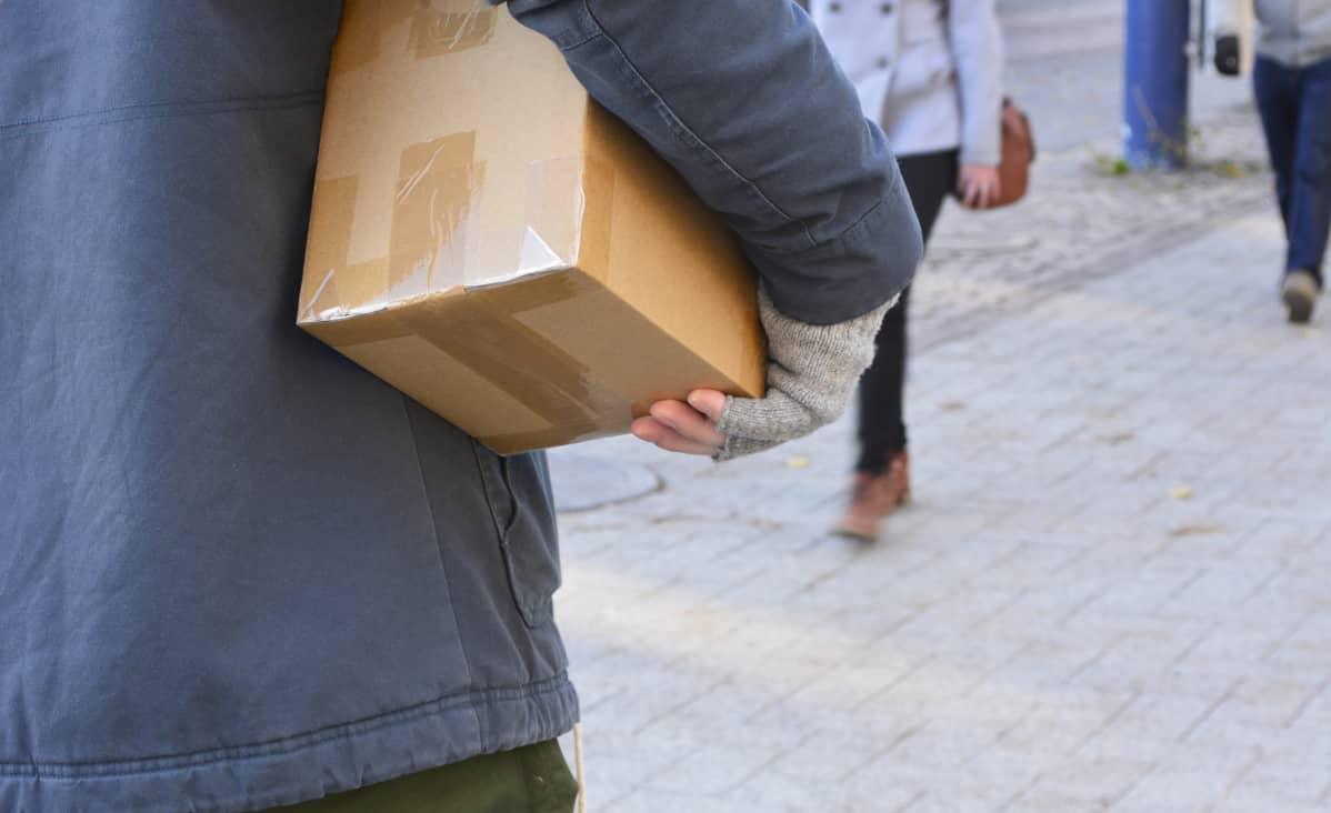 Mies kantaa ruskeaa pakettia kadun vilinässä.