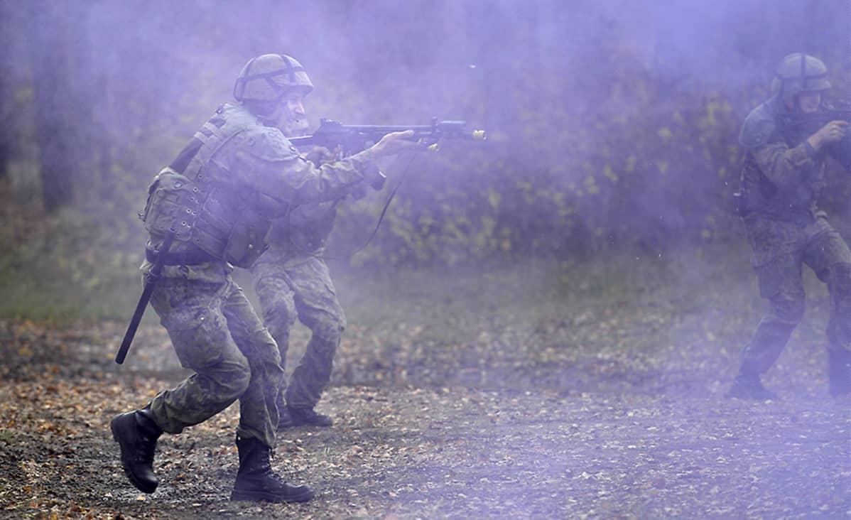 Reserviläiset sotilaspoliisit etenevät savun keskellä harjoituksessa maavoimien vuoden suurimmassa reservin kertausharjoituksessa vuonna 2014.