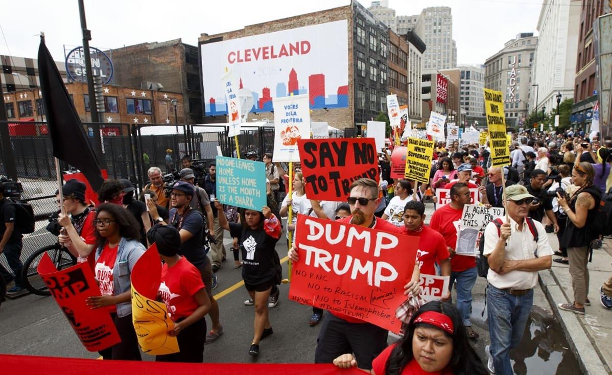 """Mielenosoittajia kadulla. Mukana kylttejä, joissa lukee muun muassa """"Dump Trump"""" ja """"Say No To Trump""""."""
