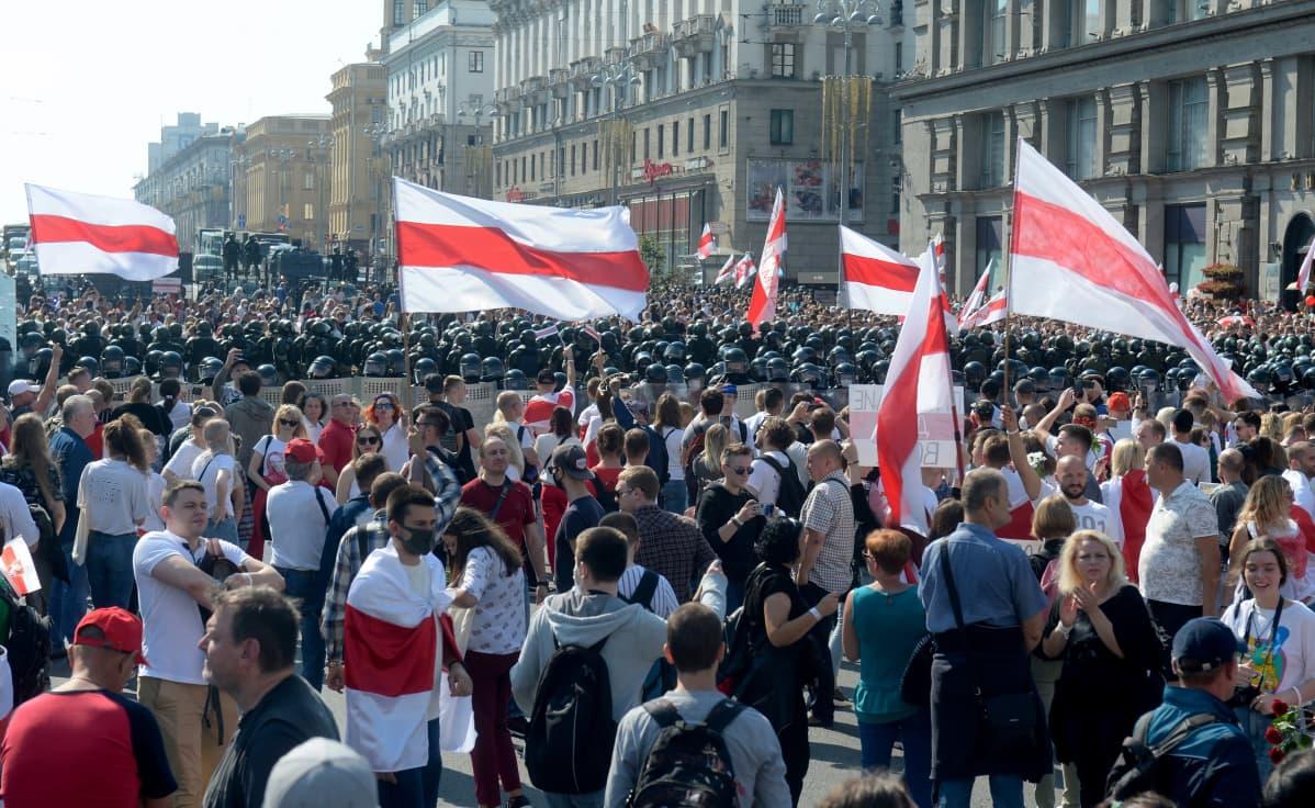 Suuri joukko mielenosoittajia seisoo kaduilla valkopunaisten lippujen kanssa mellakkapoliisien rivistön edessä.