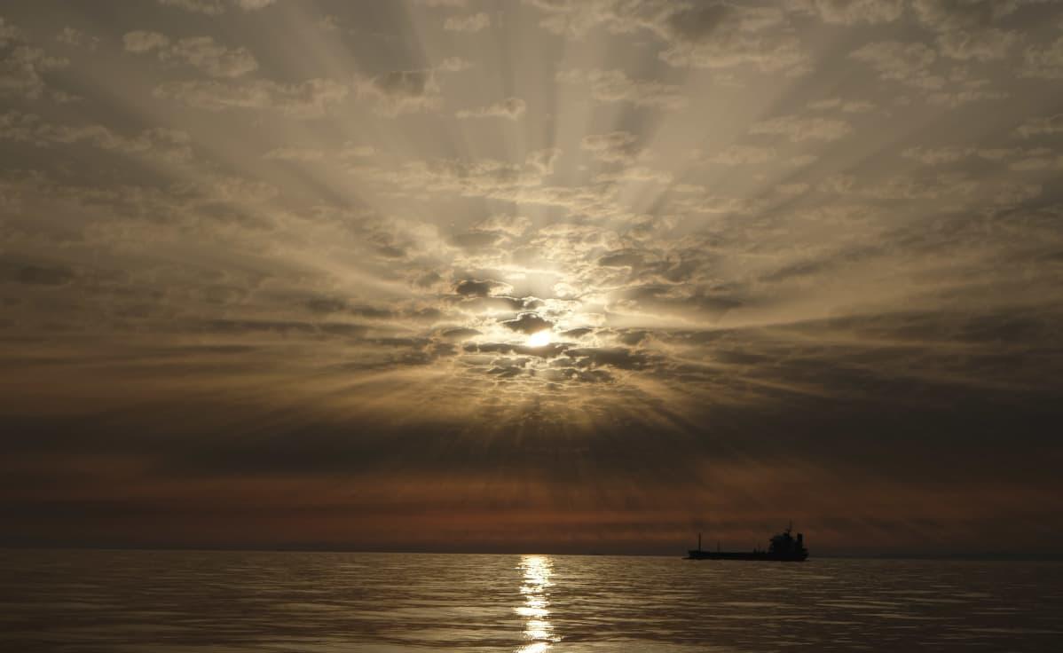 Aurinko laskee rahtilaivan taakse.