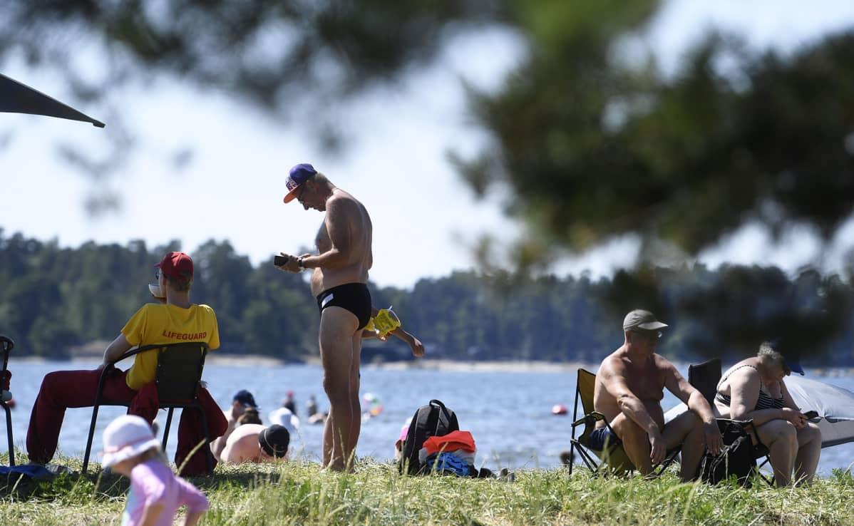 Ihmiset nauttivat lämmöstä Kallahdenniemen uimarannalla Helsingissä torstaina.