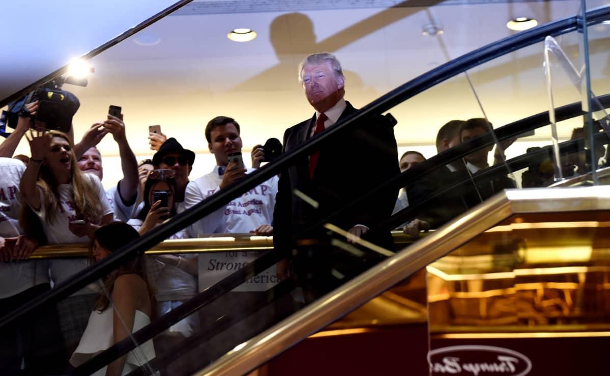 Donald Trump laskeutuu Trump Towerin liukuportaita kesäkuussa 2015.