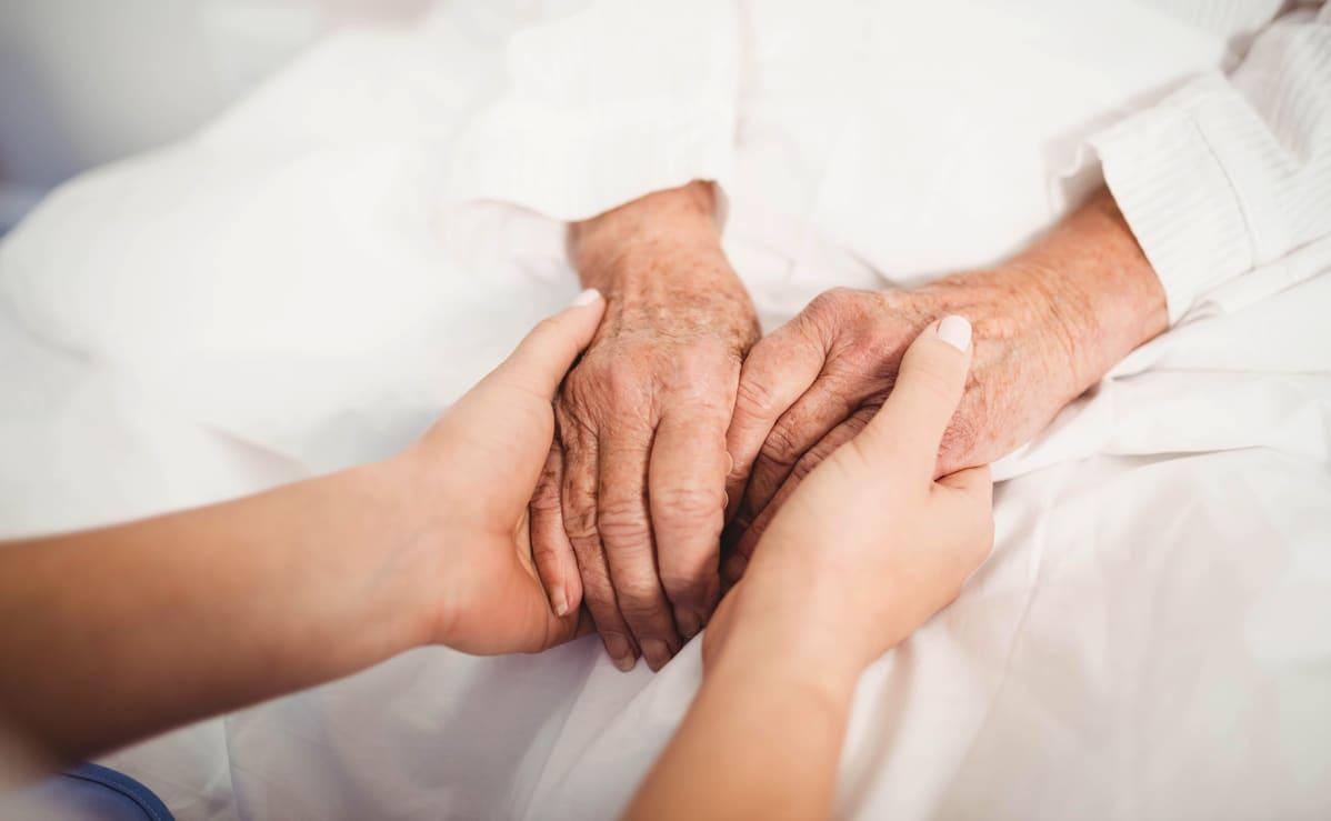 hoitaja pitää vanhuksen käsiä kädessään