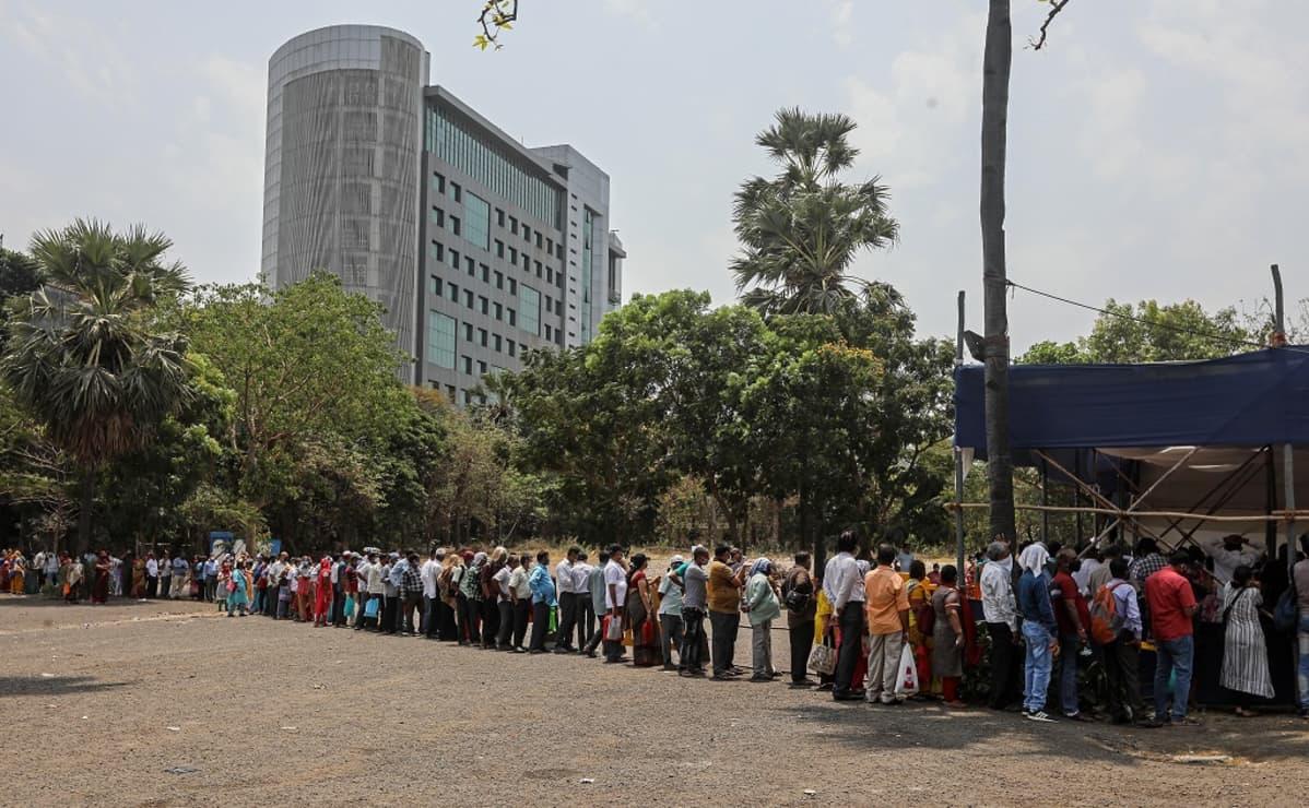 Kuvassa ihmisiä jonottamassa koronarokotetta Intian Mumbaissa. Kuvassa tiiviissä jonossa on kymmeniä ihmisiä.