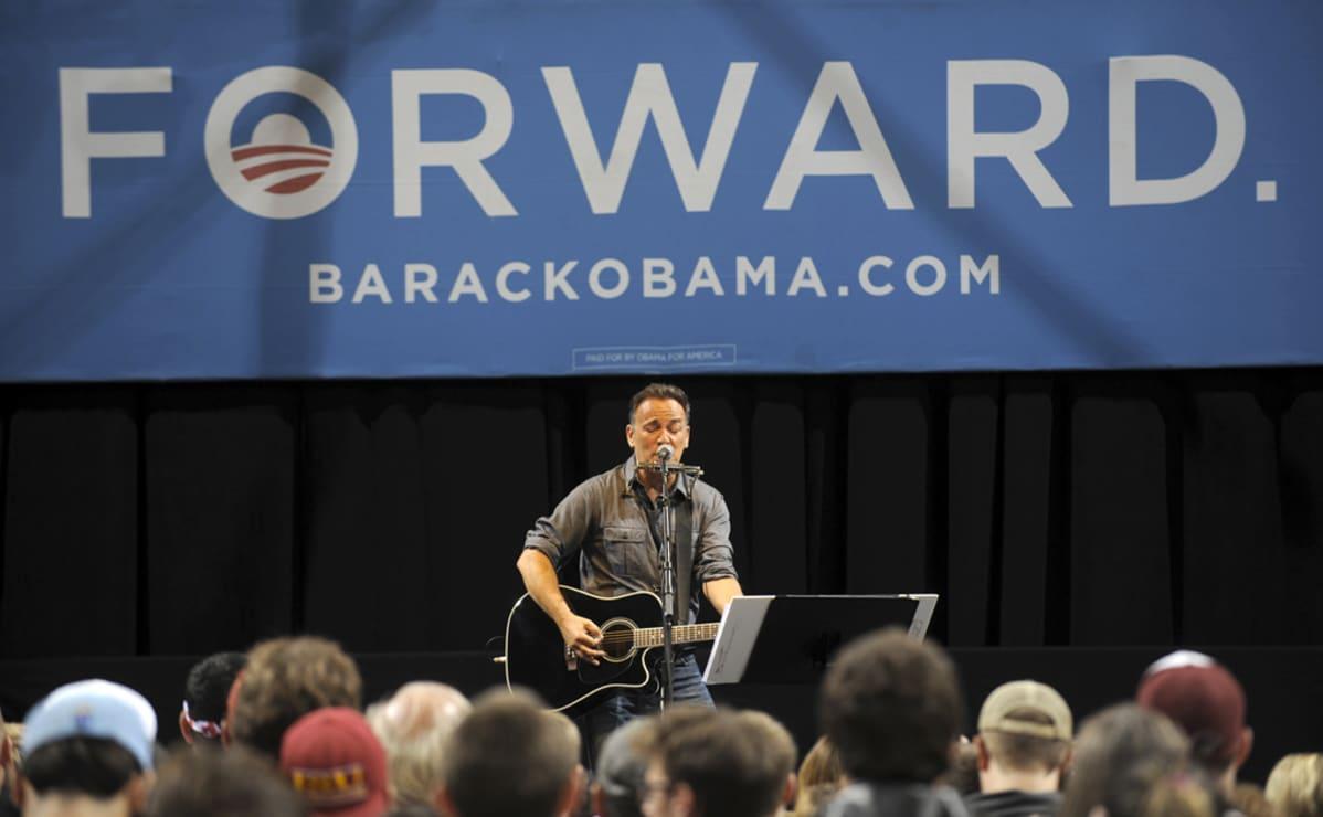 Bruce Springsteen laulaa ja soittaa kitaraa yleisölle vaalimainosten edessä