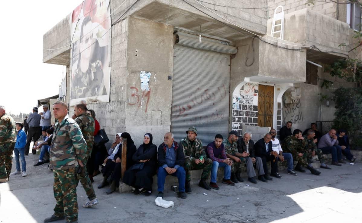 miehiä istuu rakennuksen seinustalla