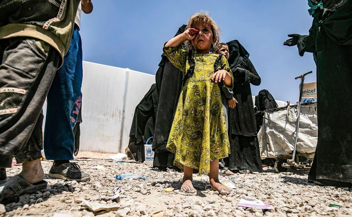 Syyrialainen pikkutyttö seisoo avojaloin kameran edessä hieroen itkuisia silmiään al-Holin pakolaisleirillä Syyriassa.
