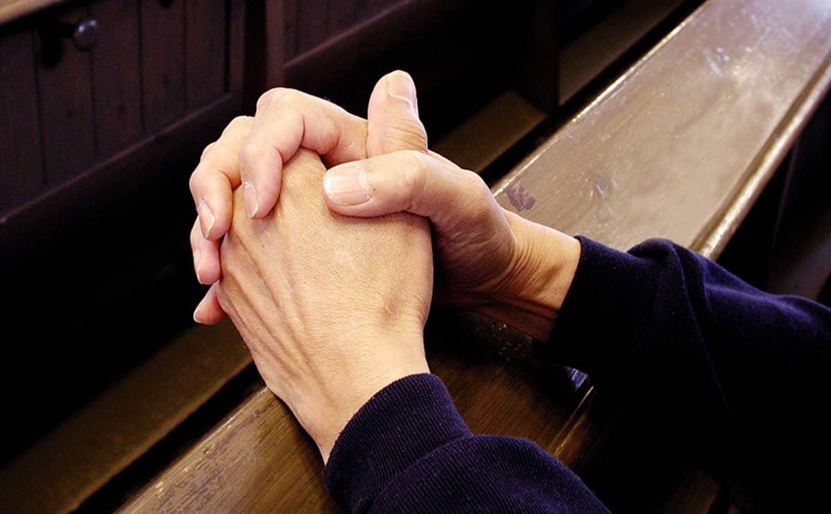 Miehen kädet ristissä kirkossa.