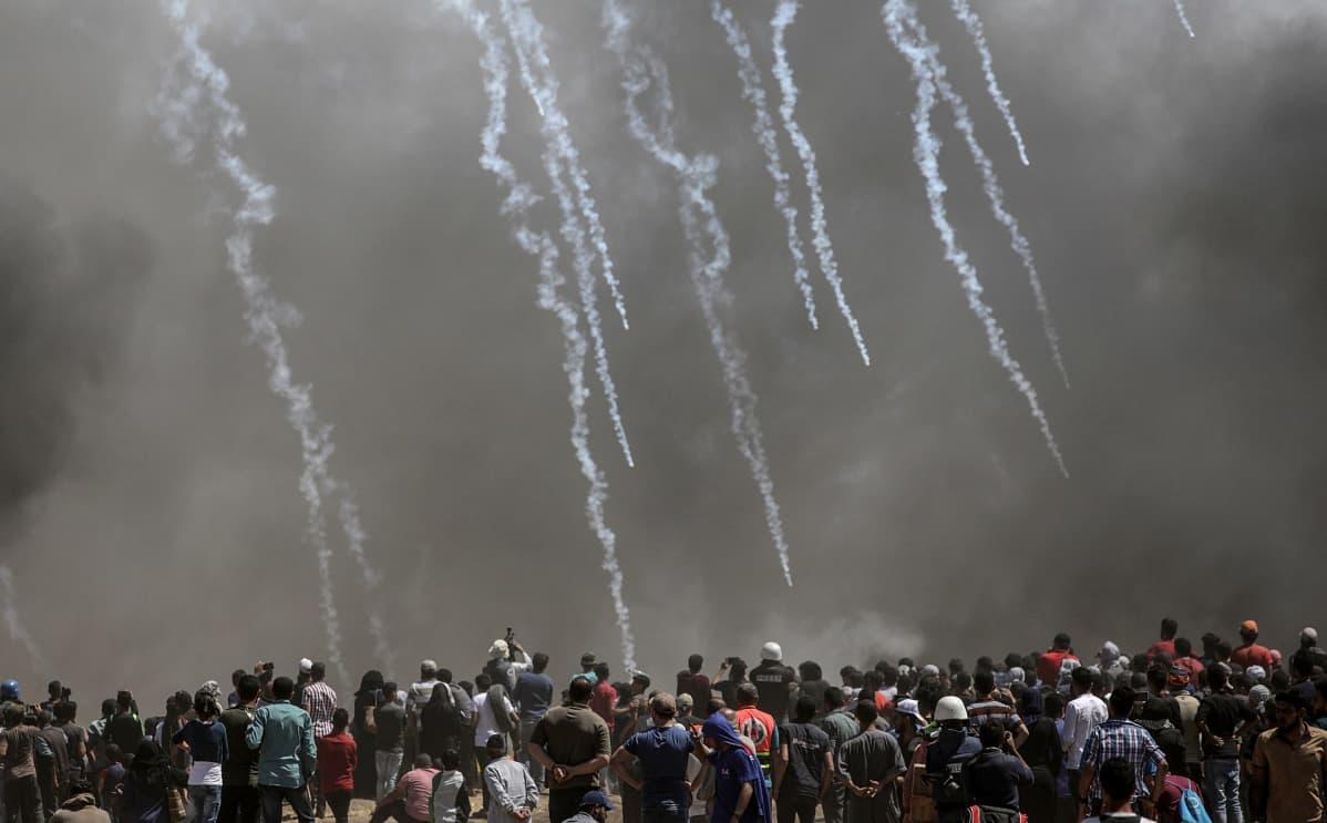 Palestiinalaismielenosoittajat juoksevat karkuun Israelin ampuessa kyynelkaasua Gazan ja Israelin rajalla.