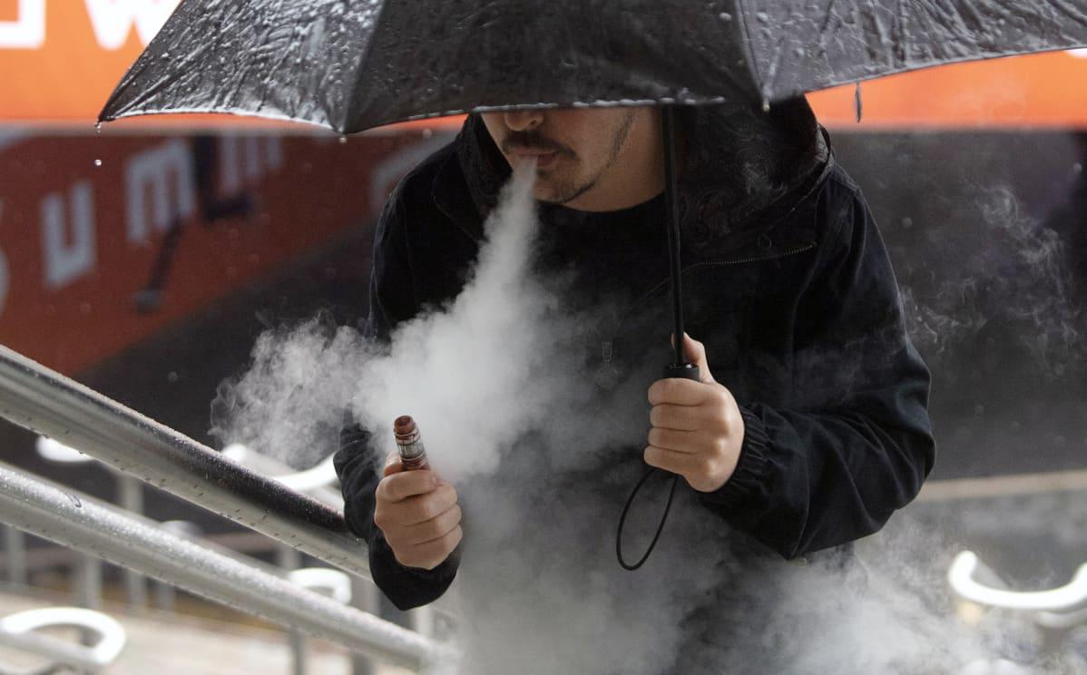 Mies polttaa sähkötupakkaa.