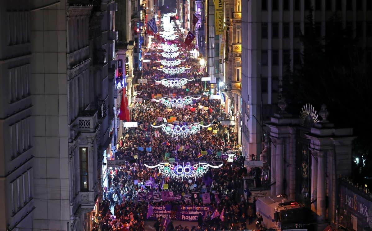 Tuhansia naisia kadulla iltahämärässä.