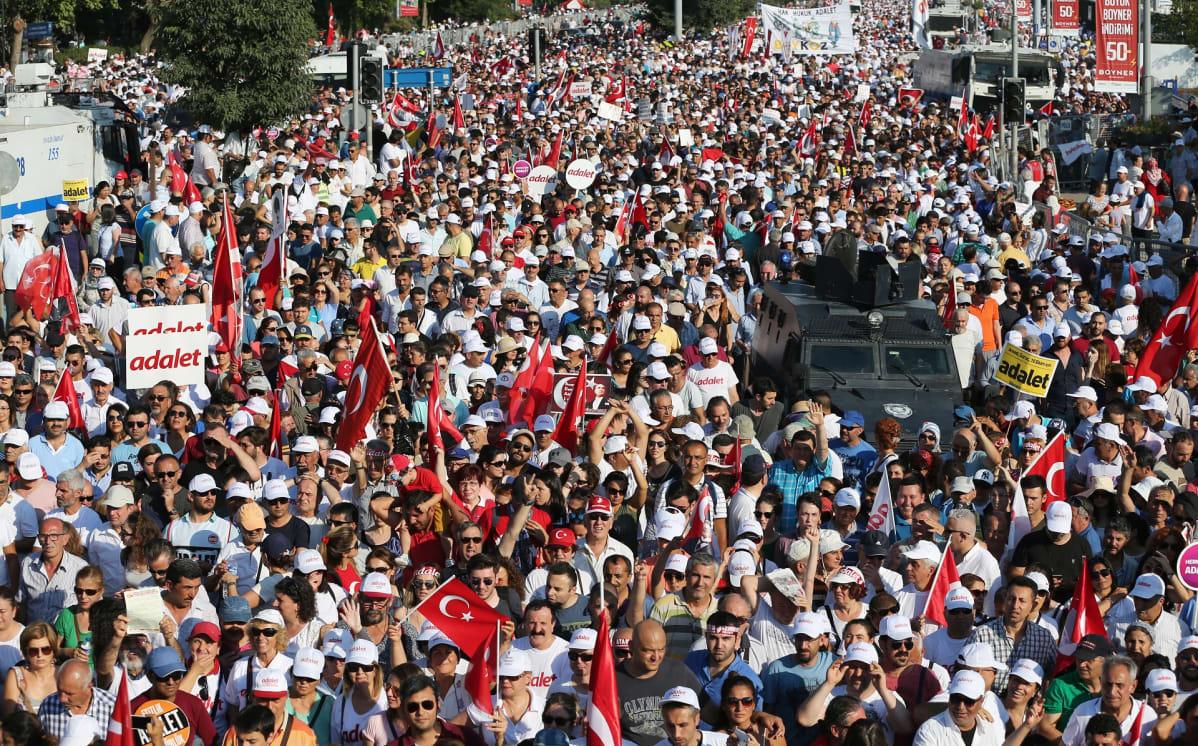 Suuri ihmisjoukko, joka kantaa lippuja ja julisteita.