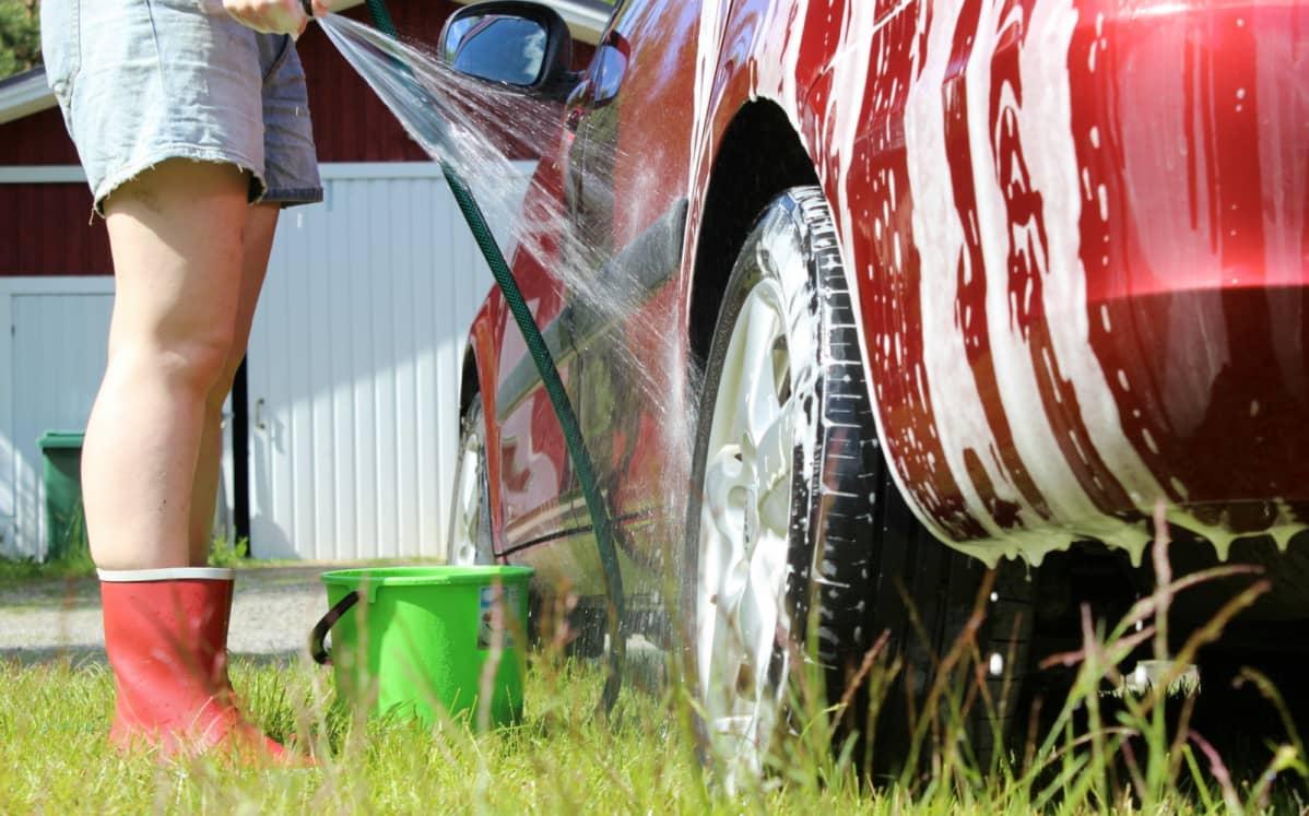 Nainen pesee autoa