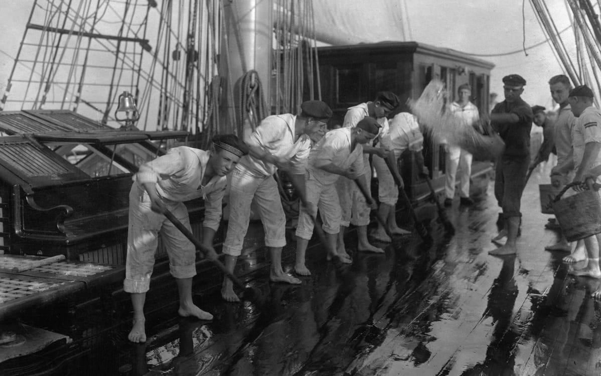 merimiehet pesevät laivan kantta
