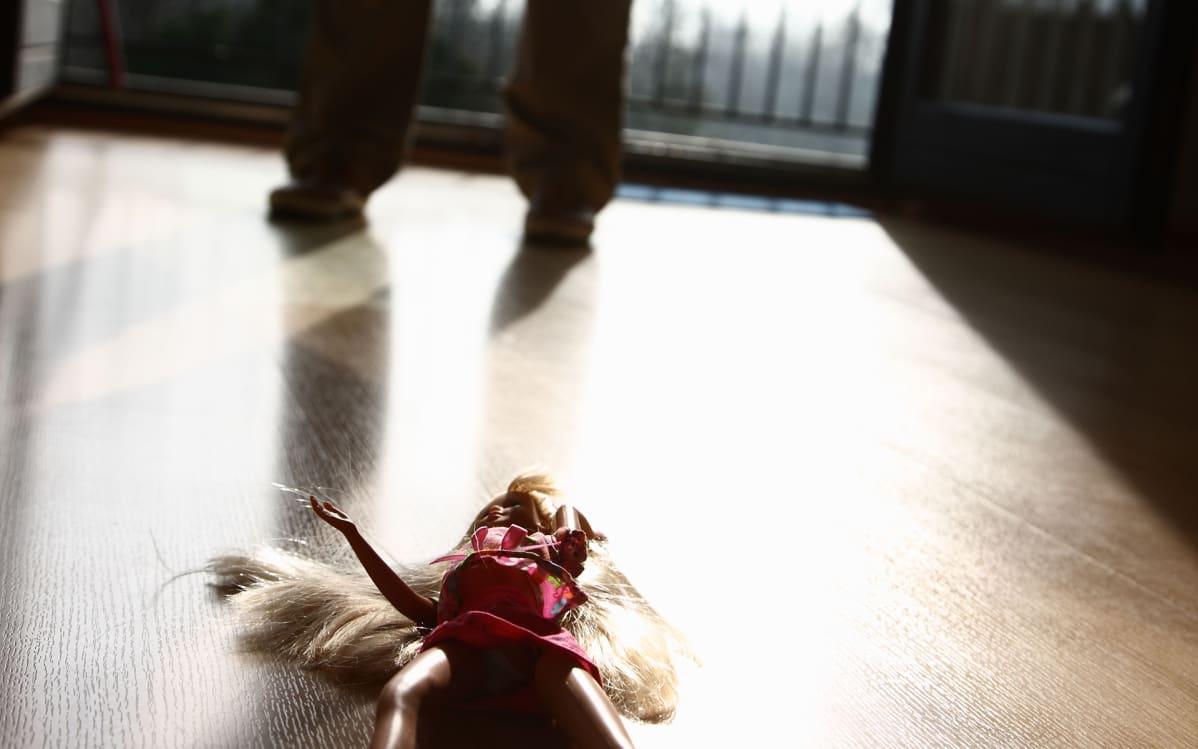 barbi lattialla ja taustalla ihmisen jalat
