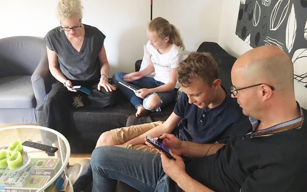 perhe kännyköillään kotisohvalla