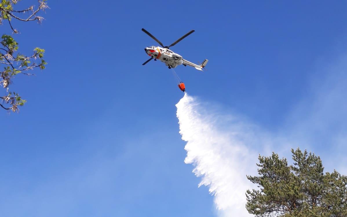 helikopteri taivaalla sammuttamassa metsäpaloa