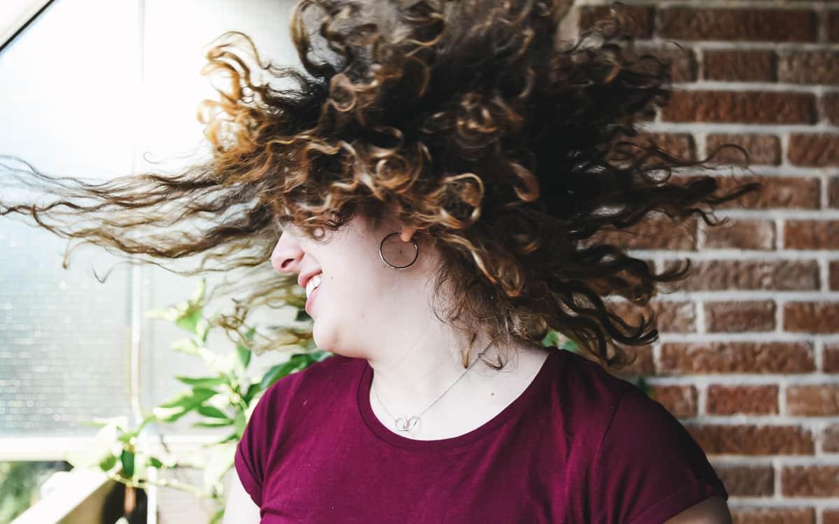 nainen heiluttaa hiuksiaan