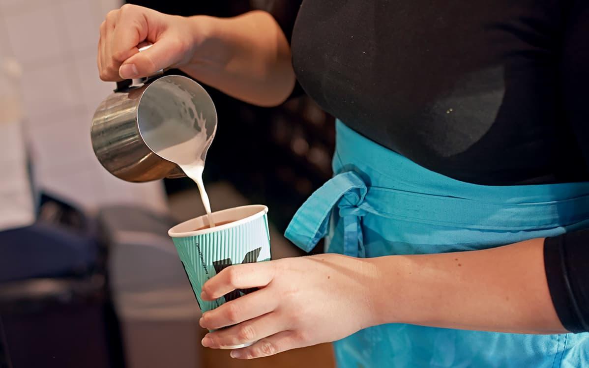 Kahvilatyöntekijä kaataa maitoa kahviin
