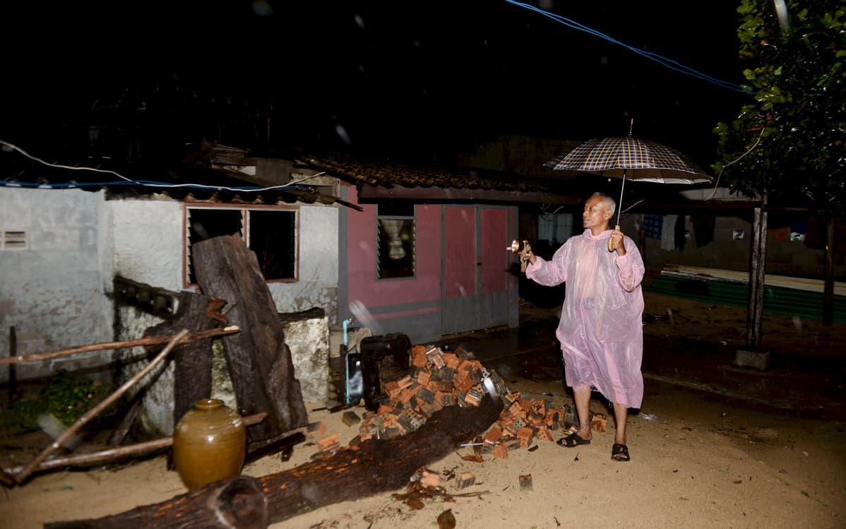 Mies tutki myrskyn tuhoja Narathiwatin maakunnassa, Etelä-Thaimaassa 3. tammikuuta.