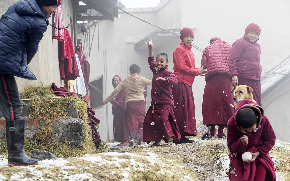 Nuoret buddhalaiset munkit leikkivät lumella viikonloppuna Nagi Gumbassa, Kathmandussa, Nepalissa.