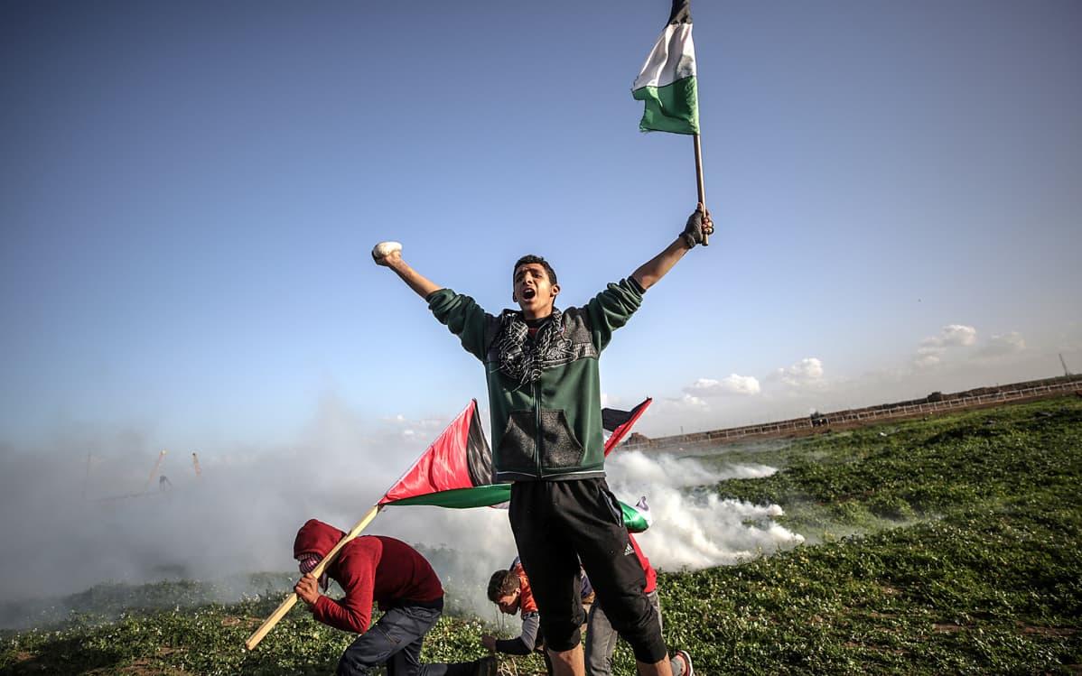 Palestiinalaiset mielenosoittajat suojautuivat Israelin armeijan kyynelkaasulta perjantain yhteenotoissa itäisessä Gazassa.