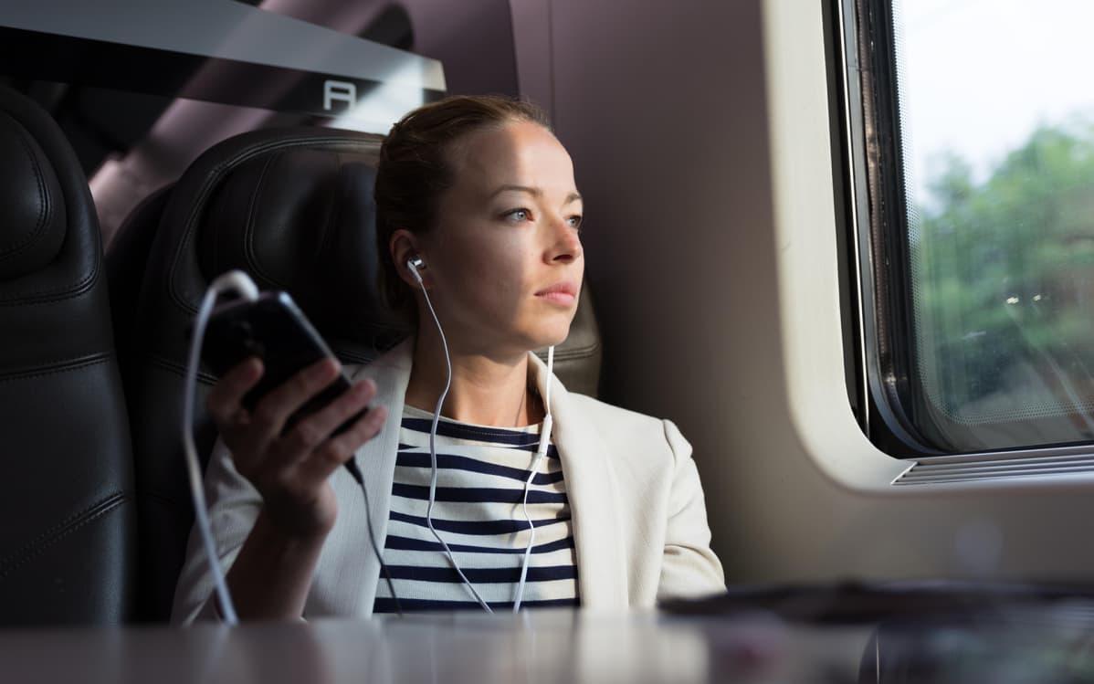 nuori nainen kuuntelee kuulokkeilla junassa