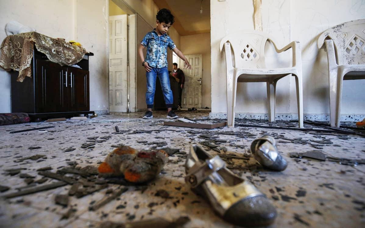 Palestiinalaispoika perheensä vahingoittuneessa asunnossa Israelin ilmaiskun jälkeen Rafahissa sunnuntaina.