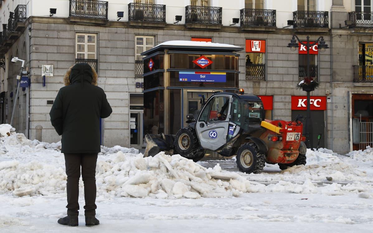 Mies katselee kun traktori auraa lunta kadulta Madridissa.