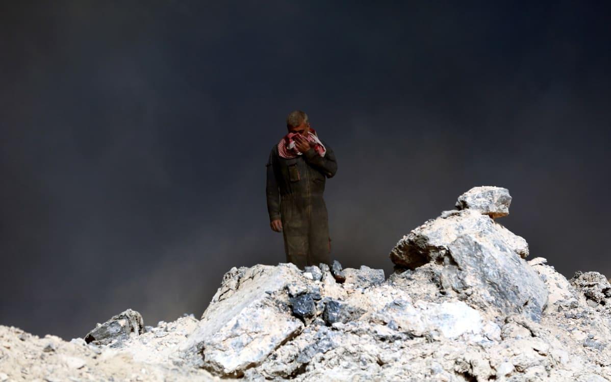 Mies siesoo kiviröykkiön päällä ja peittää kasvonsa huivilla, hänen takanaan on mustaa ja hieman harmaata savua