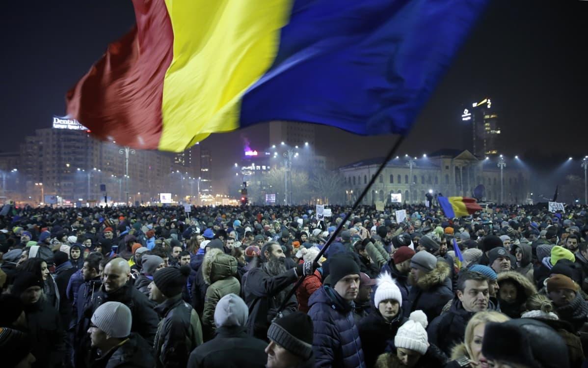Valtava määrä ihmisiä aukiolla, mies heiluttaa Romanian lippua.