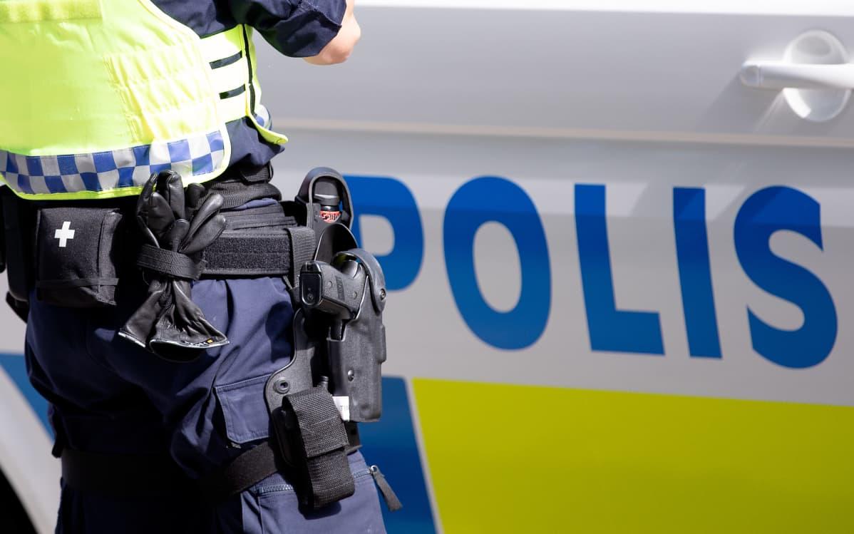 Poliisi seisoo pistooli vyöllään poliisiauton vieressä.