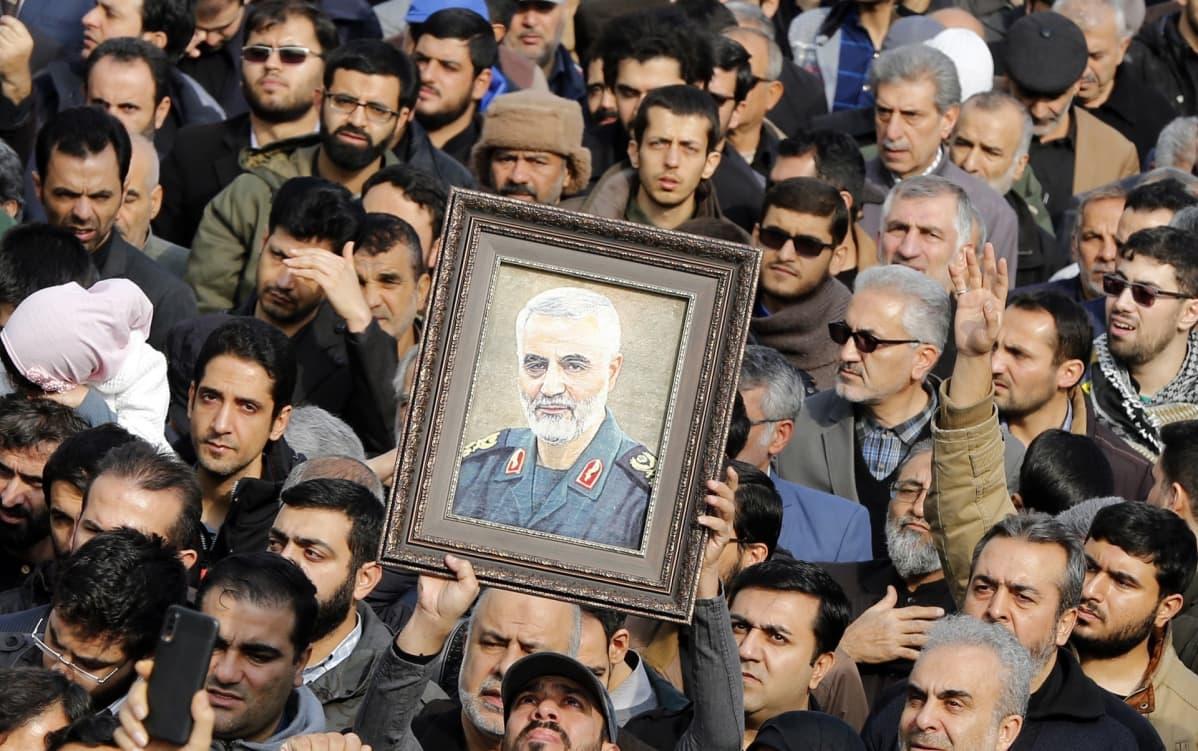 Ihmisjoukko kantaa taulua, joka esittää Qassim Suleimania.