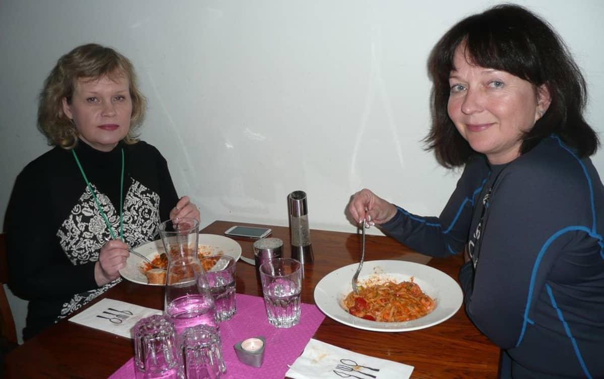 Kaksi rouvaa lounaspöydässä.