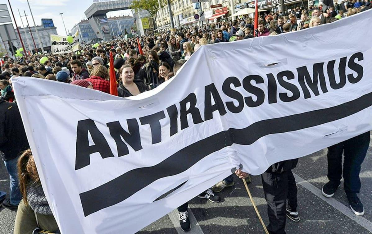 ihmisiä marssii banderollin takana