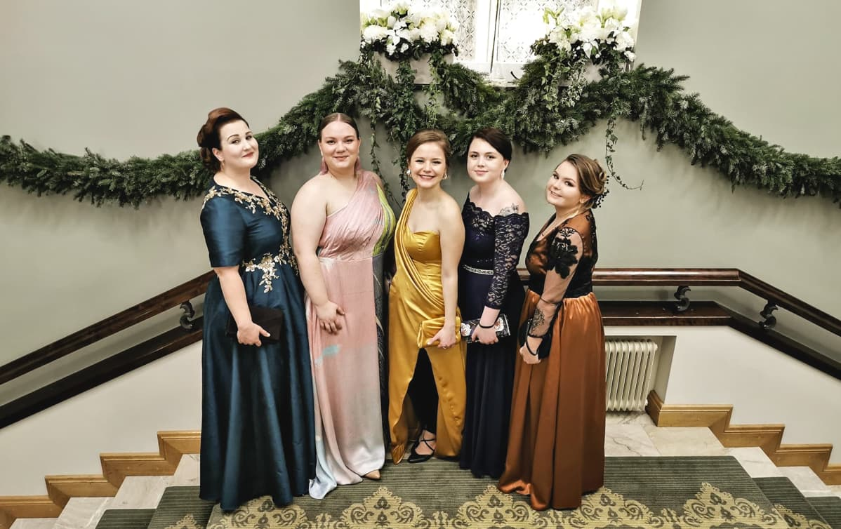 Viisi naista juhlapuvuissaan portaikossa.
