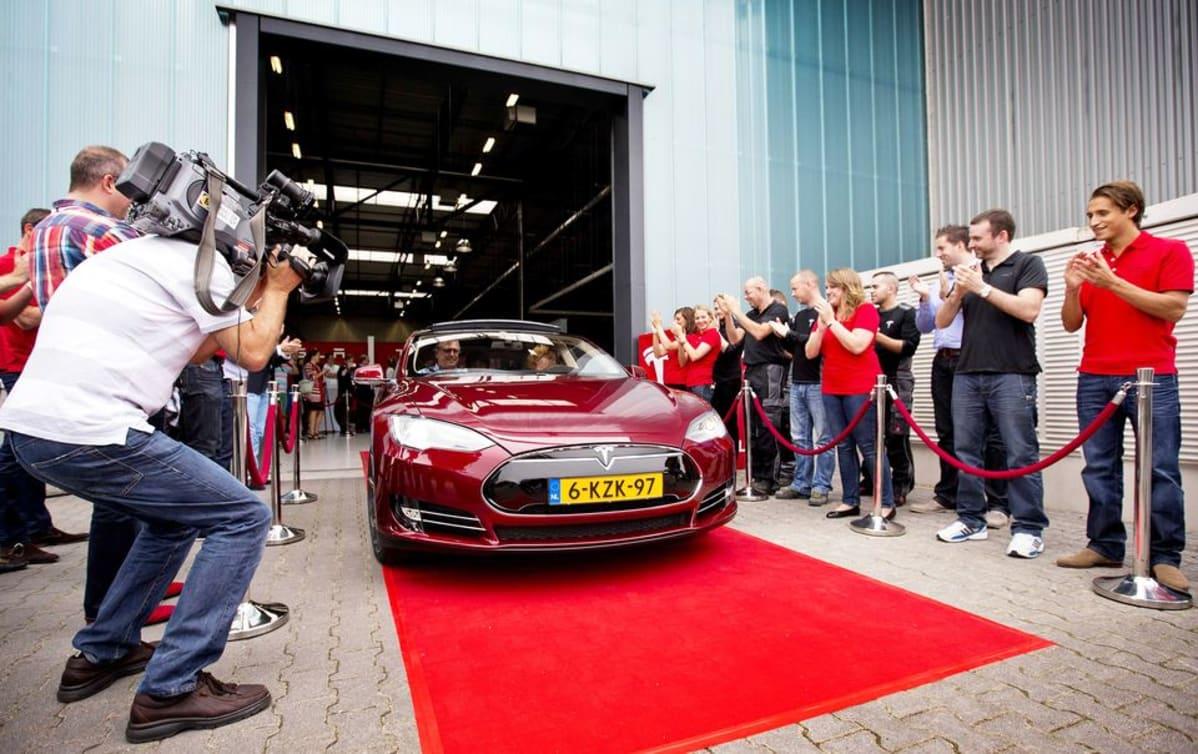 Uuden Tesla-sähköauton omistaja poistumassa autovalmistajan myymälästä Hollannissa. Kuva on vuodelta 2013.