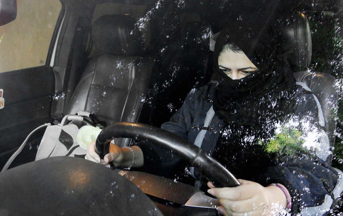 Nainen pitelee kiinni auton ohjauspyörästä Saudi-Arabiassa..