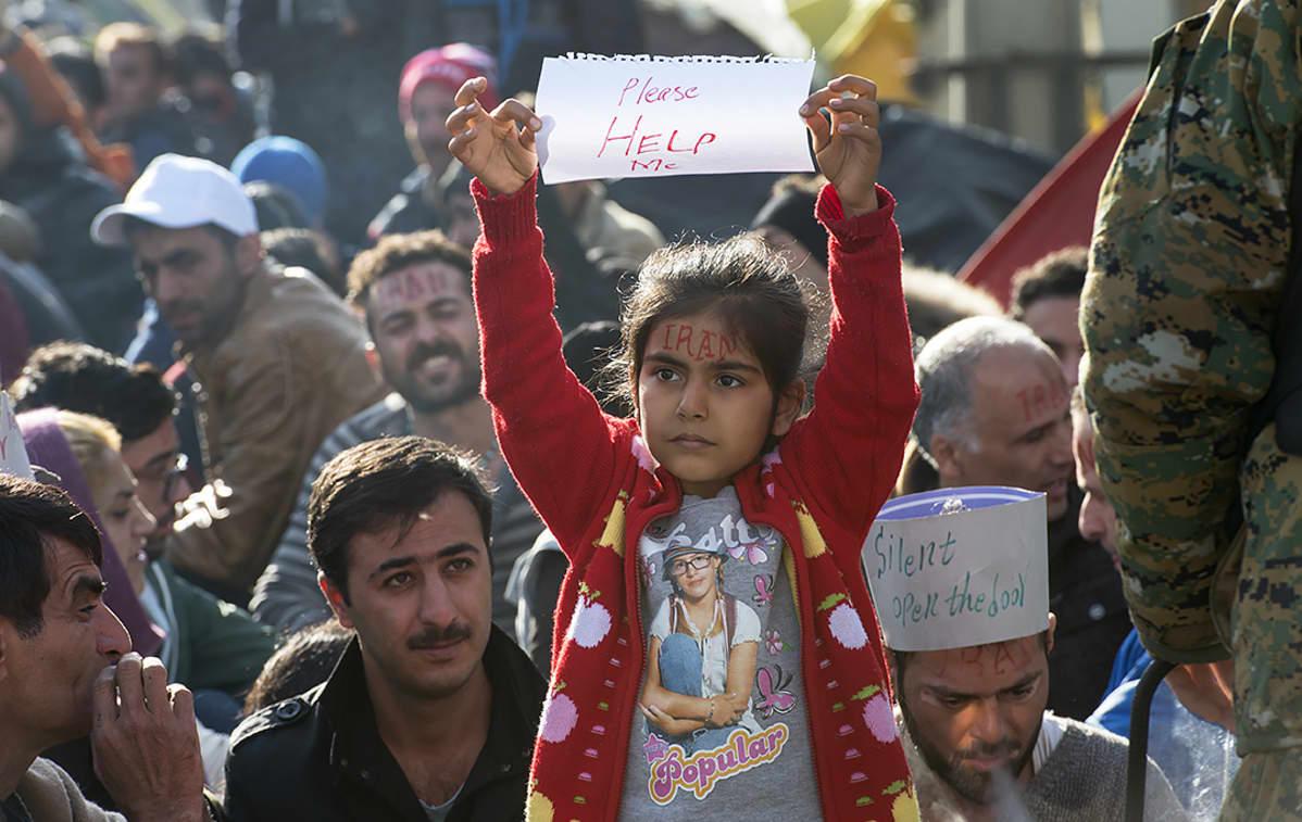 Pakolaislapsi pitelee paperia jossa lukee auttakaa minua.