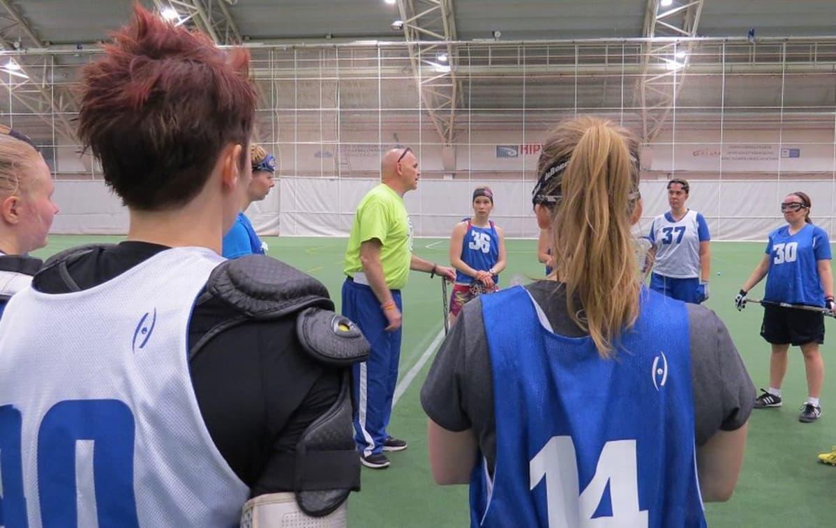 Valmentaja ohjeistaa naisurheilijoita harjoituksissa.