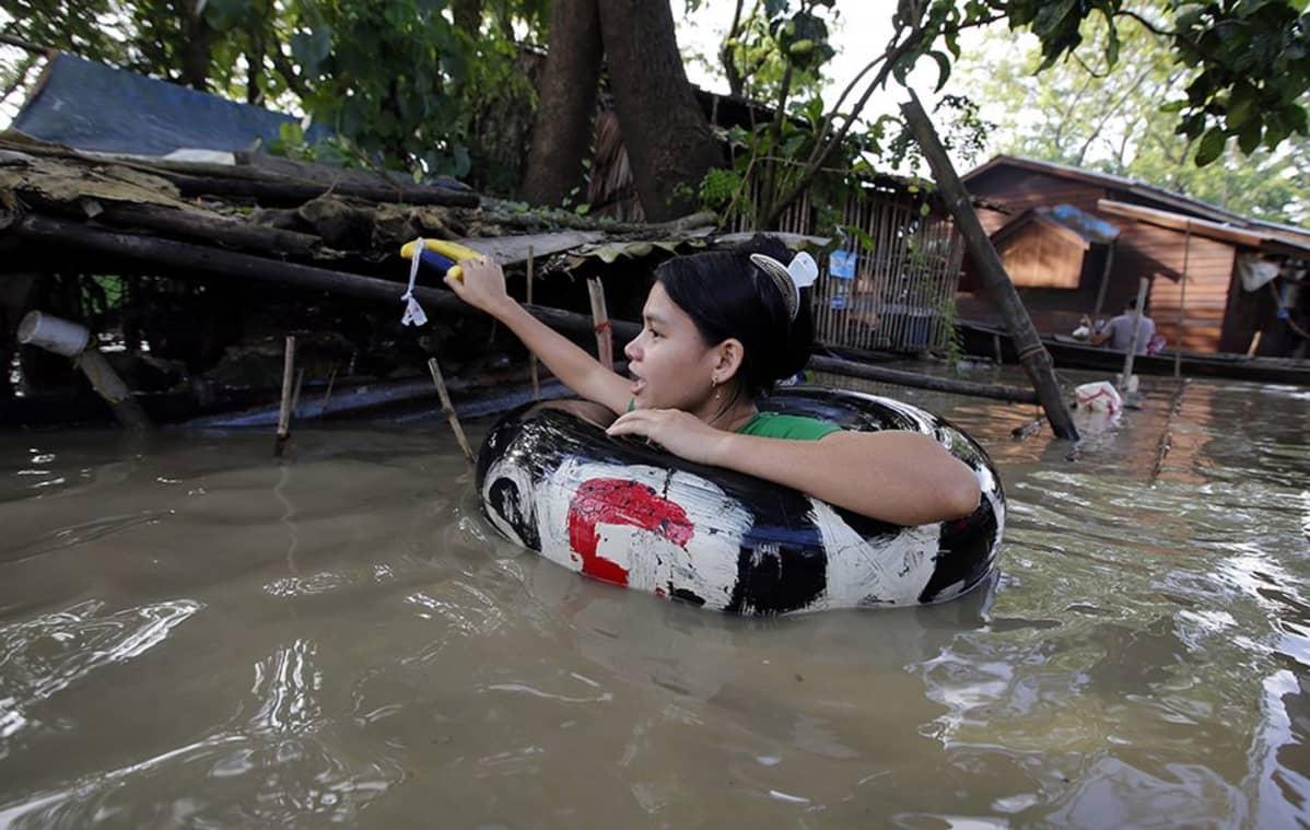 Tyttö käyttää apunaan uimarengasta liikkuessaan Nyaungdongin kaduilla