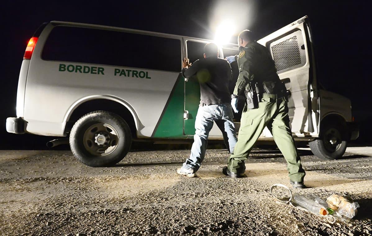 Yhdysvaltalaiset rajavartijat tarkastavat Rio Grande -joen yli laittomasti saapuneen miehen maaliskuussa 2014.